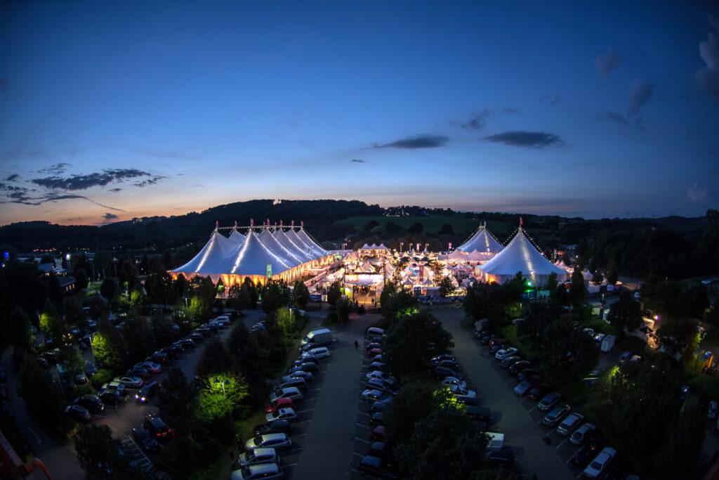 """BOCHUM -  Das Zeltfestival Ruhr ist eine 17-tägige weiße Zeltstadt, die im Spätsommer im Naherholungsgebiet """"Kemnader See"""", auf der Stadtgrenze von Bochum und Witten errichtet wird. Auf dem 25.000qm großen Gelände finden in drei Großzelten etwa 40 Konzerte, Lesungen und Comedy-Veranstaltungen pro Jahr statt. In der Abenddämmerung ist die Zeltstadt bunt illuminiert am Samstag, den 23. August 2014.  Foto: Ingo Otto / WAZ FotoPool"""